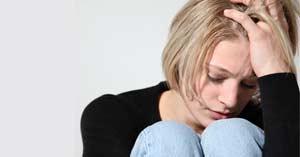 mujer sentada triste deprimida manos cabello vida dificil fondo gris