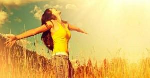 mujer sonriendo viendo hacia el cielo manos abiertas campo