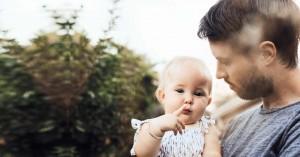 padre cargando a su bebe hija fondo arboles arbusto