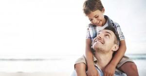 papa cargando a su hijo en su hombre fondo playa