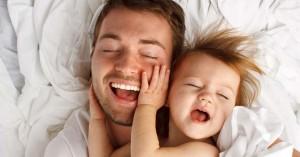 papa sonriendo feliz junto a su hijo recostado en la cama