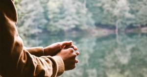 persona con manos juntas mirando un lago