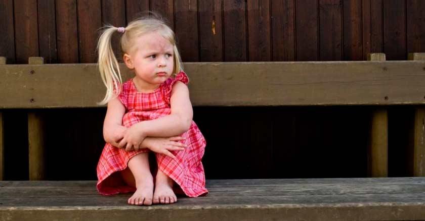 una nina bebe sentada en una banca solita con cara de molestia enojada