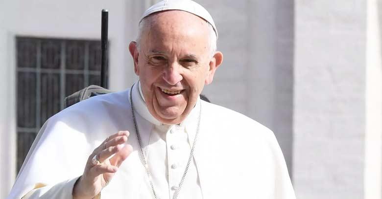 papa francisco mirando de frente saluda sonrie fondo pared