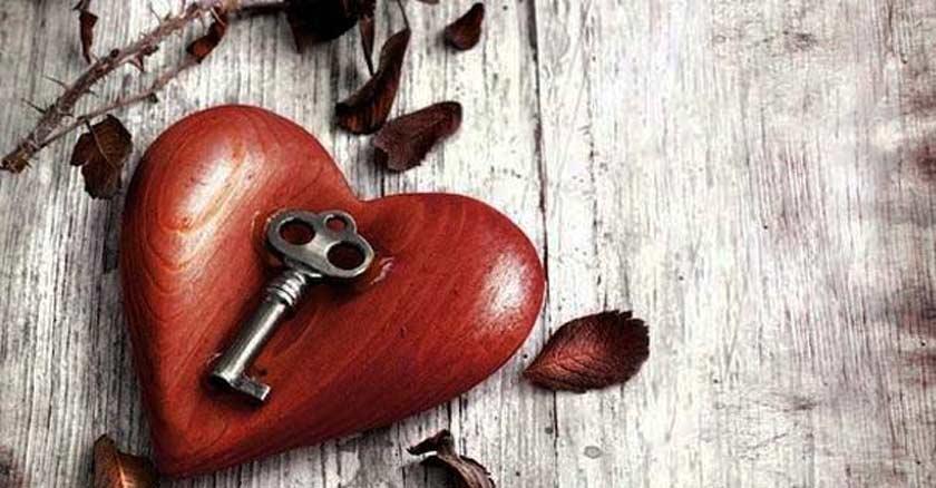 corazon rojo de madera con una llave encima mesa de madera