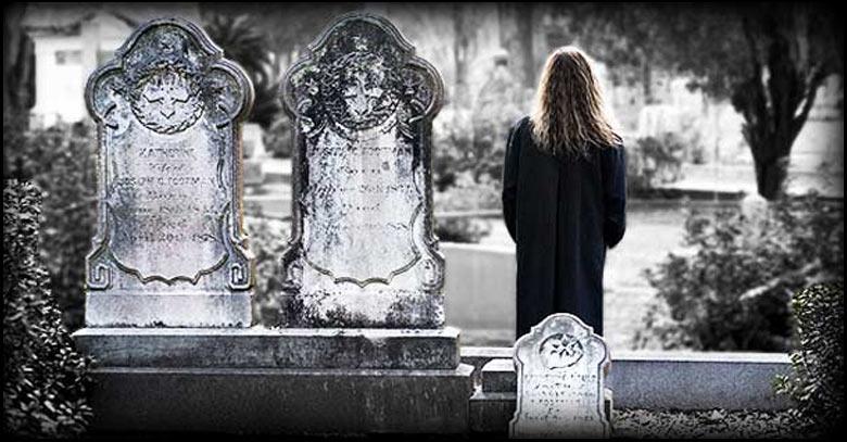 mujer de espalda en un cementerio lapidas