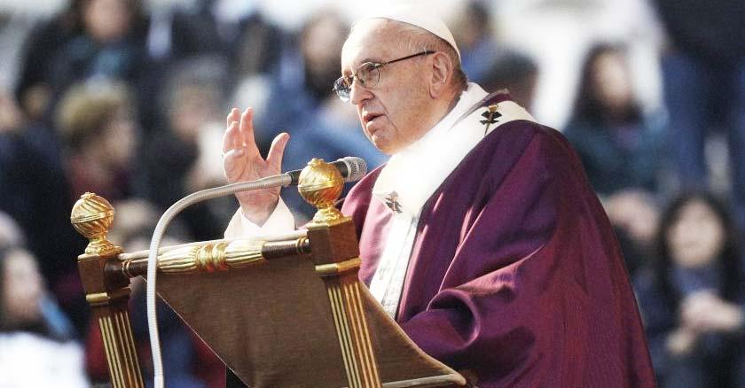 papa francisco hablando desde podio mano levantada vestidura morada
