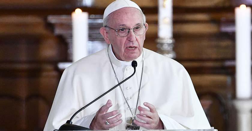 papa francisco hablando desde podio microfonos fondo marron