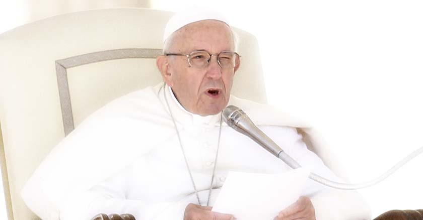 papa francisco sentado en la silla petrina sosteniendo documento en sus manos