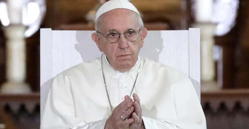 papa francisco sentado tiene las manos juntas mirando hacia el frente