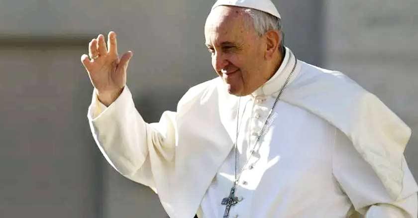 papa francisco sonriendo mientras levanta su mano para saludar fondo gris
