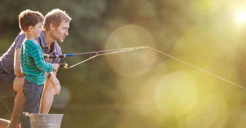 papa pescando con su hijo en la orilla de un muelle cana de pescar