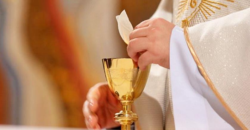 sacerdote consagrando hostia en mano copa devino eucaristia santa misa