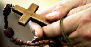 manos de hombre sosteniendo un santo rosario entre sus dedos