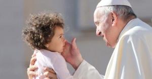 papa francisco mirando y acariciando un bebe nina con ternura