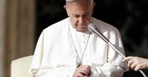papa francisco rezando con los ojos cerrados le sostienen el microfono