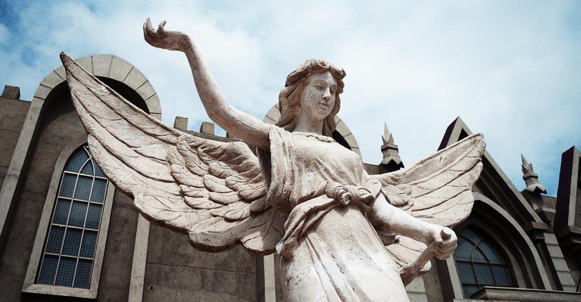 angel de la guarda estatua de pieda frente a una iglesia levanta su brazo