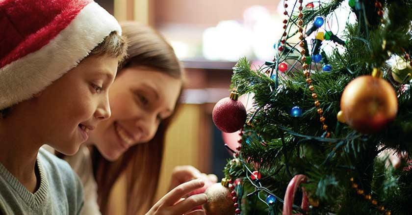 familia-reunida-madre-hijo-frente-arbol-de-navidad-sotiendo-adornos-navidenos.jpg