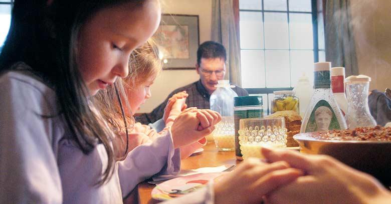 familia rezando manos juntas bendiciendo los alimentos en la mesa