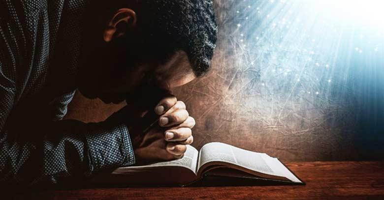 hombre orando manos unidas sobre la biblia abierta