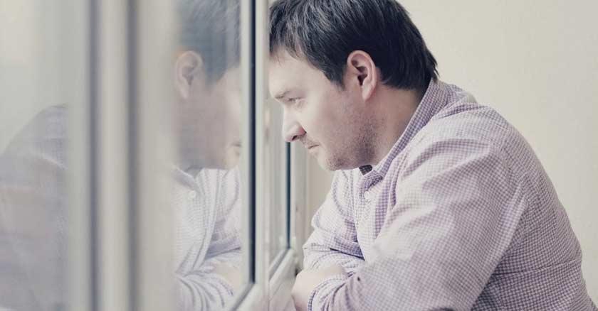 hombre rostro triste pereza desanimado mirando hacia la ventana