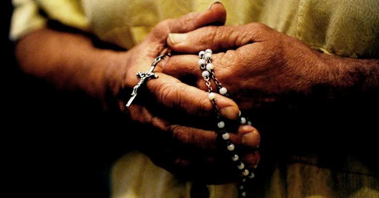 hombre sostiene rosario manos rezando entre dedos