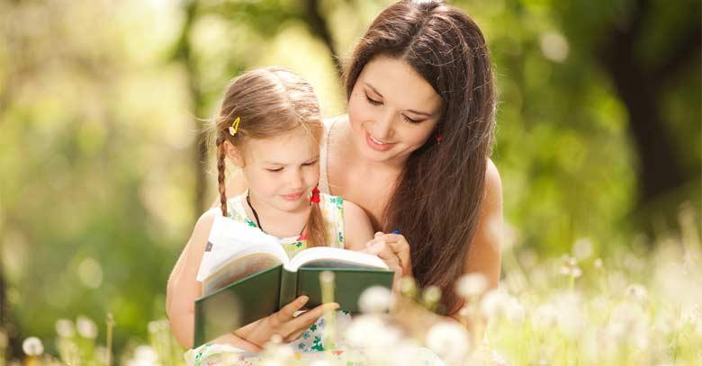 madre mostrando libro a su hija parque arboles