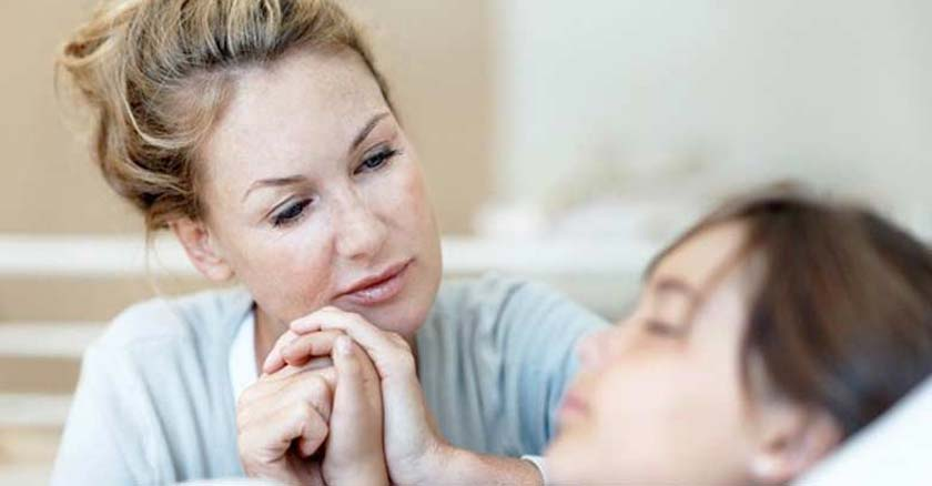 madre orando por su hija enferma acostada en cama tomando su mano