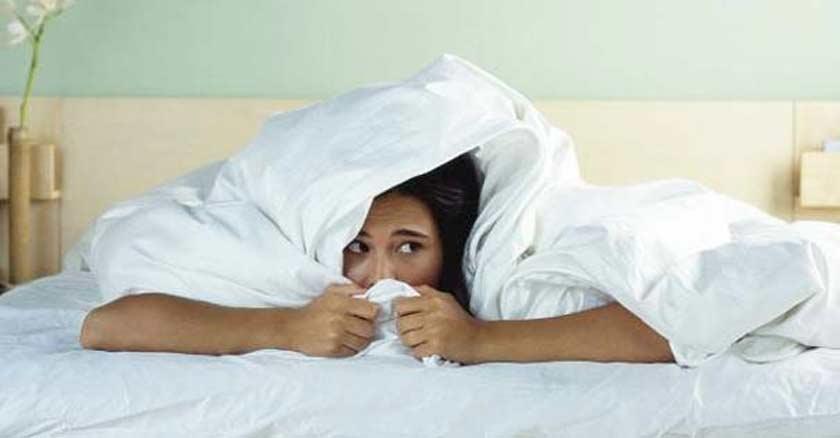 mujer arropada en una cama con rostro de miedo angustia