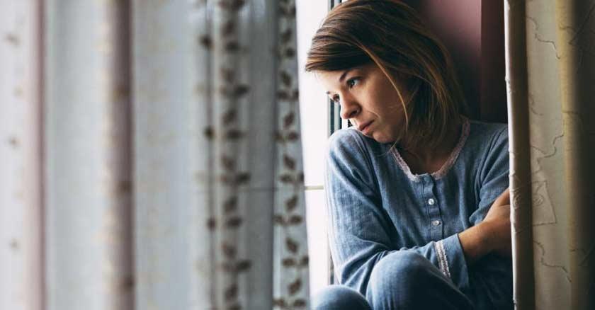 mujer con el rostro triste con depresion deprimida mirando por ventana de su cuarto