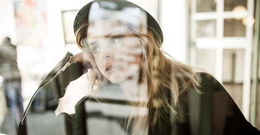mujer con gorro sentada  mirando por una ventana