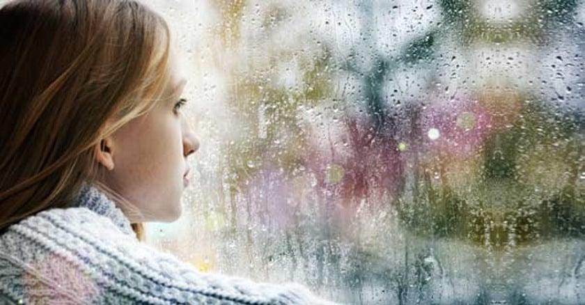 mujer mirando ventana gotas lluvia oracion sanacion interior