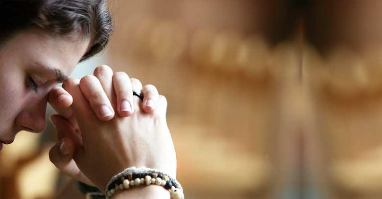 mujer orando con ojos cerrados pulsera con rosario en mano