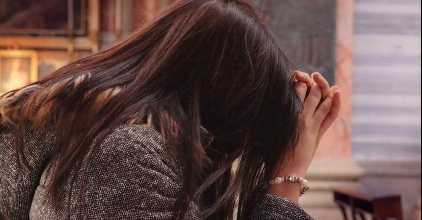 mujer orando con tristeza triste cabeza agachada manos juntas obre mesa