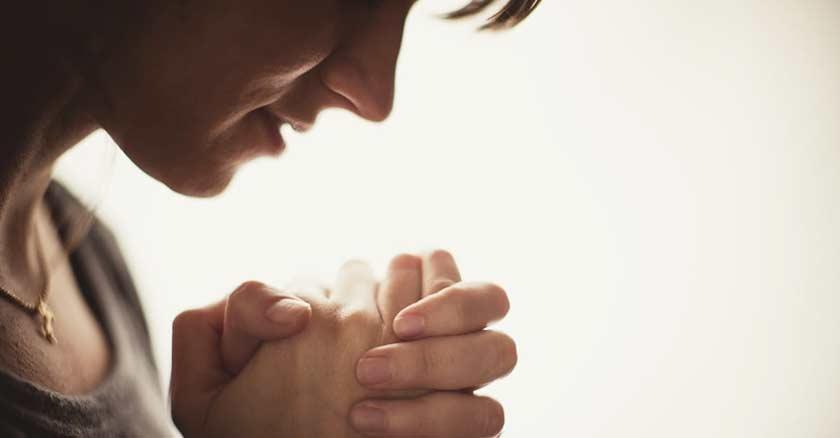 mujer orando perfil manos juntas cerradas en oracion fondo claro blanco