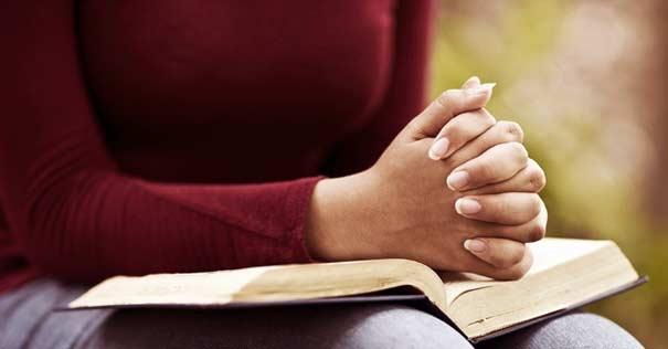 mujer rezando manos sobre biblia tocar corazon dios oracion