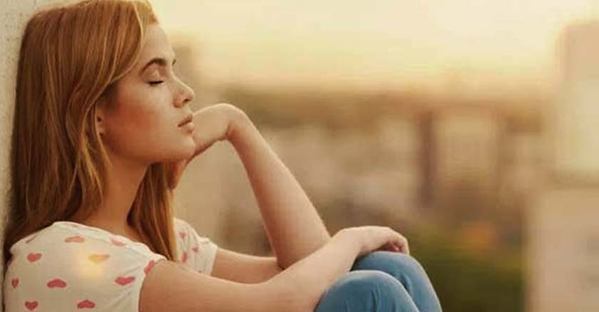 mujer sentada recostada de una pared ojos cerrado reflexionando