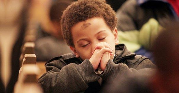 nino muchacho rezando sentado miercoles ceniza cruz frente iglesia