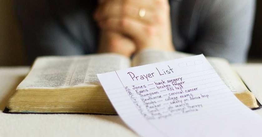 orando con las manos juntas biblia abierta lista de oracion
