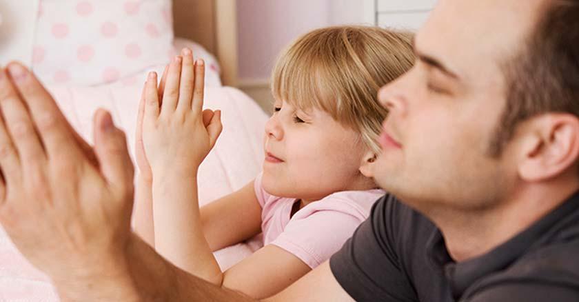 papa orando junto a su hija al lado de su cama ojos cerrados manos juntas oracion