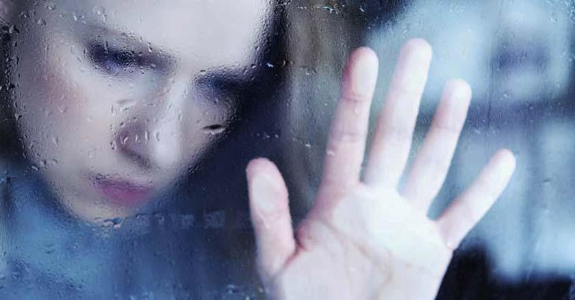 reflejo de una mujer a traves de una ventana apoyandose