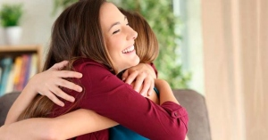 dos mujeres abrazadas sontiendo abrazo de perdon felices