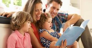familia reunida sentados en la sala felices leyendo un cuento a sus hijos dia
