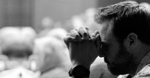 hombre rezando con las manos juntas en su frente blanco y negro