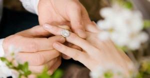hombre tomando las manos de una mujer colocando anillo de compromiso amor