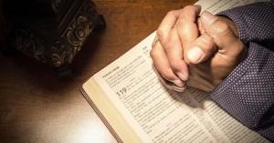 manos de hombre juntas orando sobre la santa biblia