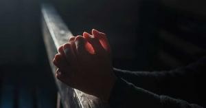 manos orando juntas en la oscuridad en iglesia asientos