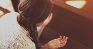 mujer orando con las manos abiertas sentada en los bancos de la iglesia