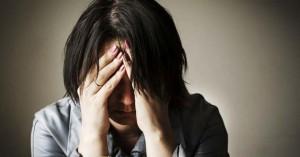 mujer preocupada angustiada con las manos en la cabeza triste sola