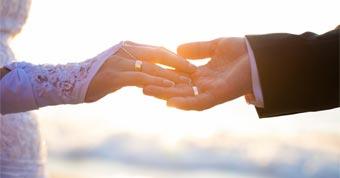 novios esposos tomados manos atardecer sol horizonte